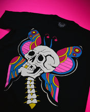 Cargar imagen en el visor de la galería, A short sleeve black t-shirt with a white skull plus neck vertebrae. The skull has one gold tooth. Behind the skull are butterfly wings and antennas. The colors on the wings are pink, red, gold and blue.