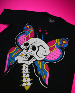 A short sleeve black t-shirt with a white skull plus neck vertebrae. The skull has one gold tooth. Behind the skull are butterfly wings and antennas. The colors on the wings are pink, red, gold and blue.