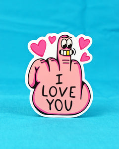 "Vinyl sticker of a hand of a pale ivory skin tone sticking up its middle finger with the back of the hand facing forward. Four pink hearts surround the raised finger. A cheesy grinning face is located on the tip of the finger, featuring 1 golden tooth in its smile, a raised unibrow, and excited eyes. On the hand is written ""I LOVE YOU""."