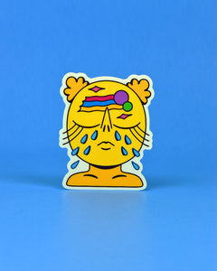 Vinyl Sticker of a yellow, crying feminine creature, shown from their collarbones upwards. Eyes are shut with extremely long eyelashes, crying 5 tears out of each eye. Janice has pursed lips, a long raised nose, and 2 puffy space buns. On their forehead are a purple and green circle followed by a pink, blue, and yellow rainbow with 2 4-pointed pink stars off to either side of the rainbow.