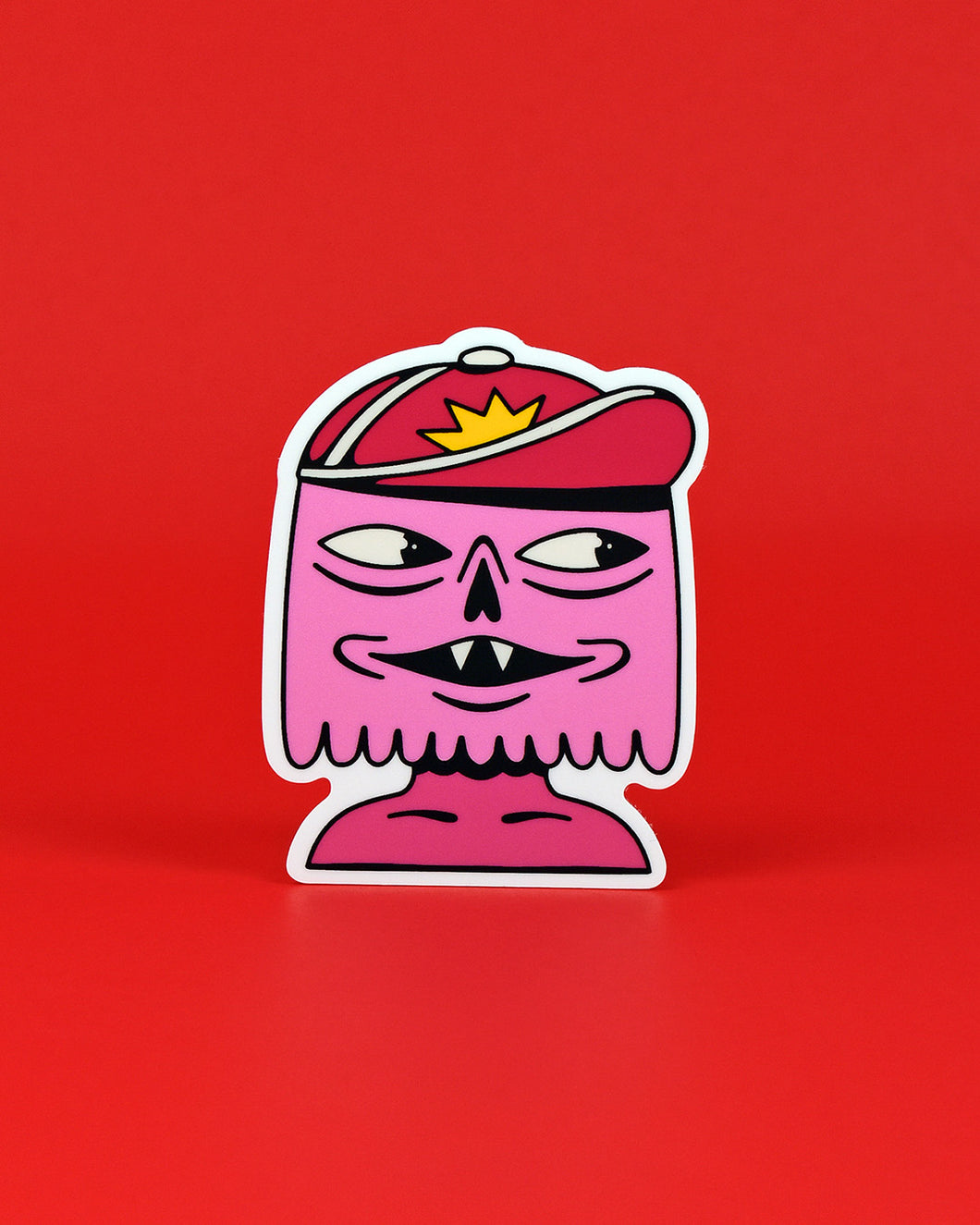 Vinyl sticker of a pink boyish creature shown from the neck up. Jax's face is a half-oval with a scalloped-edged chin. 2 almond shaped eyes veering off to the right, eye bags below, a hollow nasal opening like that of a skull, and a slightly open and mischievous mouth showing 2 fangs. Jax is wearing a dark pink baseball cap with white edges and a yellow star on the crown.
