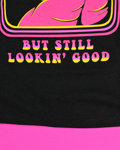 A black short sleeve t-shirt that reads Misunderstood above the graphic and But Still Lookin' Good below the graphic in pink to gold font. The graphic in the center is a skull in a pink cloak sporting sunglasses with a gold frame. His left hand is sticking out of the cloak making a fist and his index finger and thumb are sticking out. Behind him he is holding a sickle that has a pink shaft and gold blade.