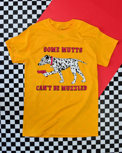 Yellow background with a black and white spotted Dalmatian dog growling on all fours and facing left. In the dogs left hand paw is a red pistol. The dog has a red collar with a round name tag. In red font it reads Some Mutts above the dog and Can't Be Muzzled below the dog.  All on a gold short sleeve t-shirt.  Back drop is black & white checkered with a red vertical accent.