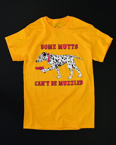 Yellow background with a black and white spotted Dalmatian dog growling on all fours and facing left. In the dogs left hand paw is a red pistol. The dog has a red collar with a round name tag. In red font it reads Some Mutts above the dog and Can't Be Muzzled below the dog.  All on a gold short sleeve t-shirt.  Back ground is all black.