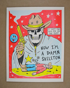 A print of a skeleton with a brown cowboy hat with 2 bullet holes in it and a chin strap with gold tips. The skeleton is wearing a light blue cloak with a gold sheriff star pinned on it and he is holding a gold smoking gun in his right brown gloved hand. At the bottom is a cowboy laying in the desert holding 2 white daisies. The wording says I Left the Old Me in the Dust...Now I'm a Damn Skeleton. The background is hot pink with white stars. There is a round blue smiley face to the left of the gun.