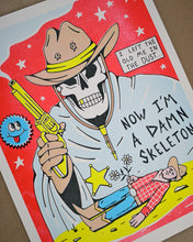 Load image into Gallery viewer, A print of a skeleton with a brown cowboy hat with 2 bullet holes in it and a chin strap with gold tips. The skeleton is wearing a light blue cloak with a gold sheriff star pinned on it and he is holding a gold smoking gun in his right brown gloved hand. At the bottom is a cowboy laying in the desert holding 2 white daisies. The wording says I Left the Old Me in the Dust...Now I'm a Damn Skeleton. The background is hot pink with white stars. There is a round blue smiley face to the left of the gun.