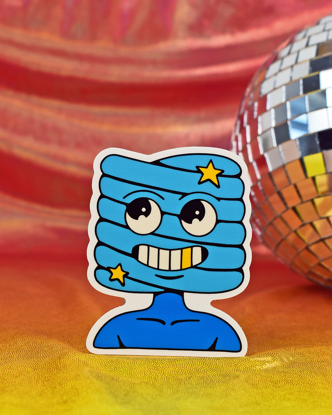 Sheepishly handsome or devilish deviant, you decide. From the twisted creativity that lives in the mind of his creator, Crocodile Jackson., this vinyl sticker features a blue creature with a stacked spiral face featuring round happy eyes, a large grin with 1 gold tooth, and 2 yellow stars. Character is shown from the neck up.