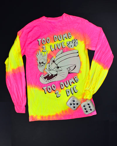 The back of a bright pink & yellow swirling tie dye long sleeve t-shirt. Black and white print that reads Too Dumb 2 Live at the top and Too Dumb 2 Die at the bottom. The center has a snarling bob cat head with a flame coming out of it's mouth. A skull is in the flame. 2 dice are above the bob cat.