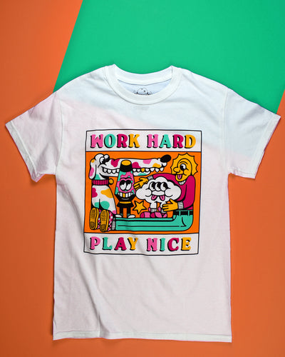 A white short sleeve t-shirt with Work Hard printed at the top of the graphic in the center of the front of the shirt. Play Nice is printed at the bottom. Each letter is a different color of either pink, mint green, hot pink or yellow. The center graphic is a cartoon of a spotted dog with a very long snout, a lava lamp, Cloudia and person with very long legs. All in the same colors as the letters.