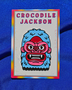 2 inch enamel pin called Yeti that is just his head surrounded by light blue fur with intense eyes that are circled with a thick brow ridge. His pink and red face has 2 small ears, flared nose and large open mouth displaying all his fangs. The pin is secured to a white 2.5 x 3.5 inch card that reads Crocodile Jackson at the top in pink and a tie dye type striped boarder in blue, white, red, pink and yellow.