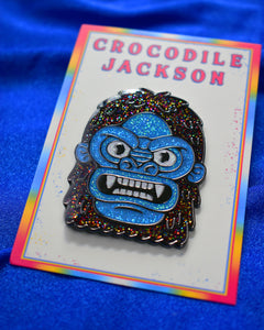 2 inch enamel pin called Yeti that is just his head surrounded by black glitter fur with intense eyes that are circled with a thick brow ridge. His blue glitter face has 2 small ears, flared nose and large open mouth displaying all his fangs. The pin is secured to a white 2.5 x 3.5 inch card that reads Crocodile Jackson at the top in pink and a tie dye type striped boarder in blue, white, red, pink and yellow.