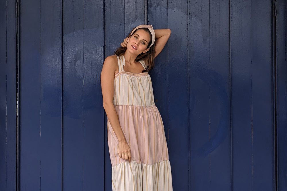 Model standing in a tiered pink and mauve striped dress and a knotted headband of similar fabric.