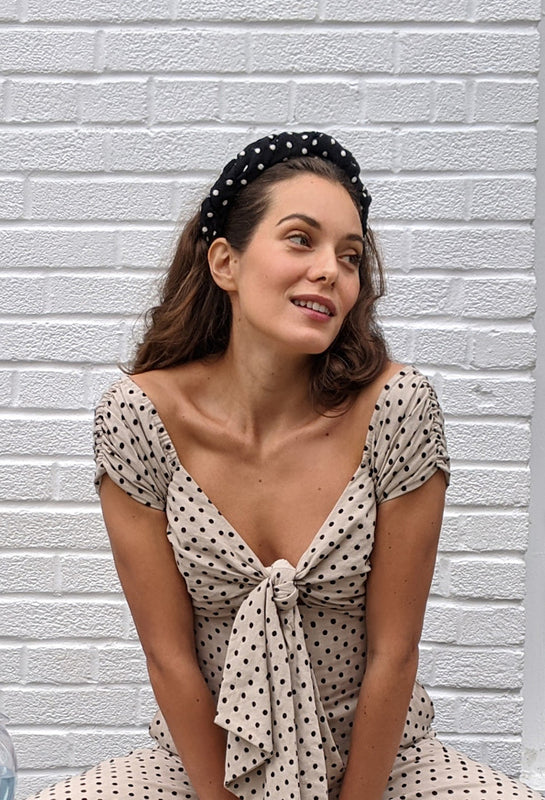 Model seated in a nude polka dot jumpsuit and a twisted headband in black with white polka dots.
