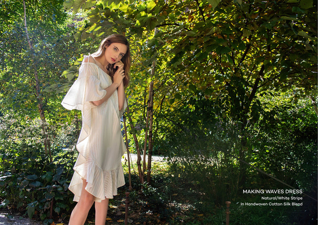 Pg 7 of lookbook: Model in white dress in front of trees.
