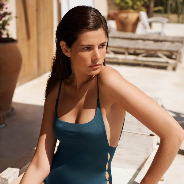 EVARAE Yoli Swimsuit Flattering Shape. Side cut out detail and open low back in Blu Tropico. Sustainable swimwear. Resort 20