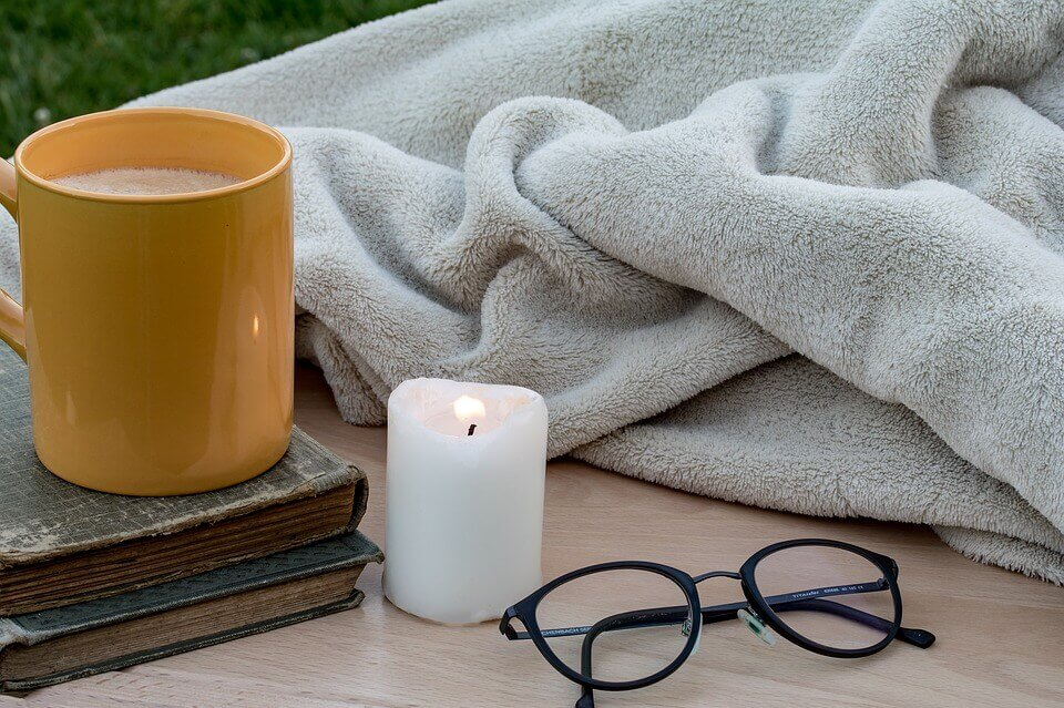 gray blanket next to cup of coffee and a candle