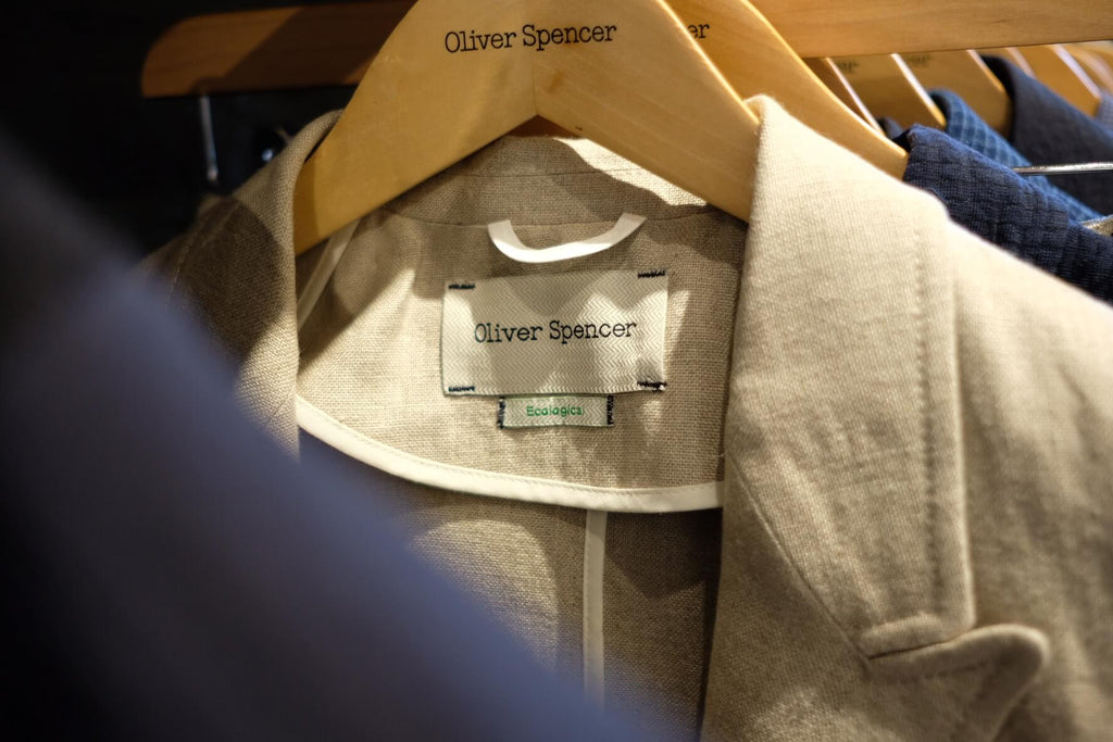 A close-up image of an Oliver Spencer linen jacket displaying an organic cotton tag.
