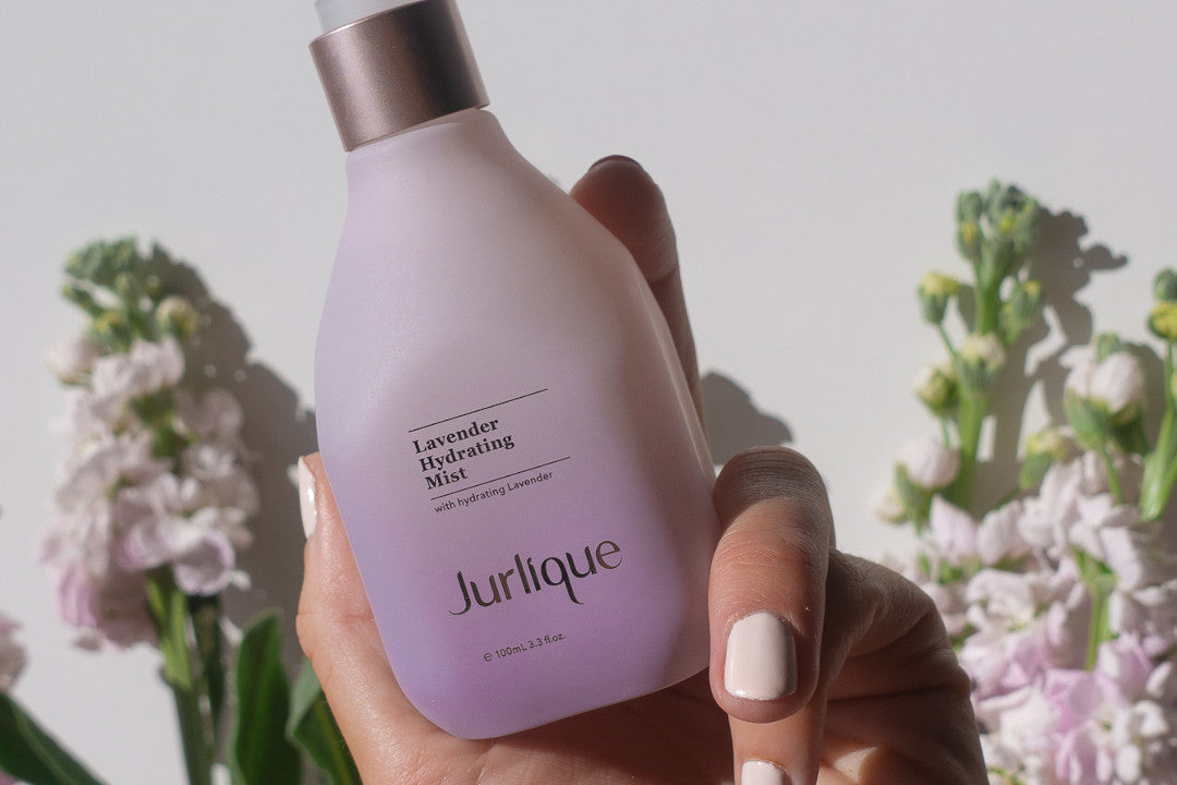 Woman's hand holding purple bottle of Jurlique Lavender Hydrating Mist in front of a backdrop of flowers