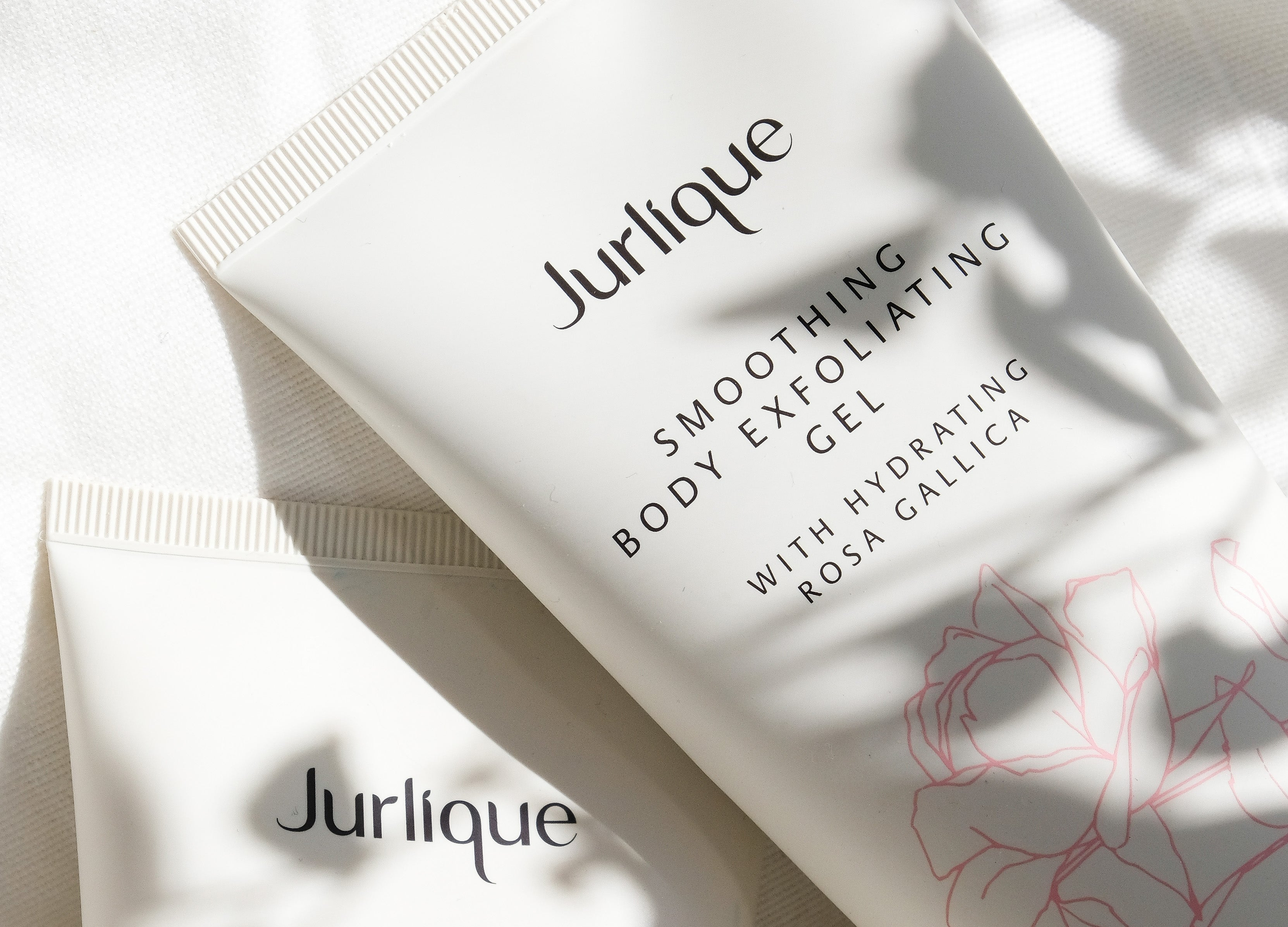White bottles of Jurlique body care products with a shadow of flowers