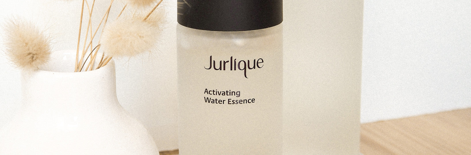 Bottle of Jurlique Activating Water Essence next to plant in a white vase