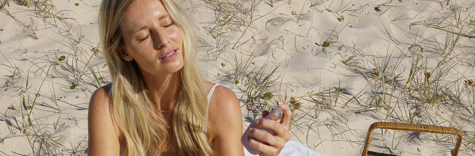 Woman with blonde hair sitting on the beach and spraying face mist onto her face