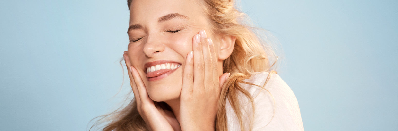 Blonde woman smiling and pressing hands to cheeks