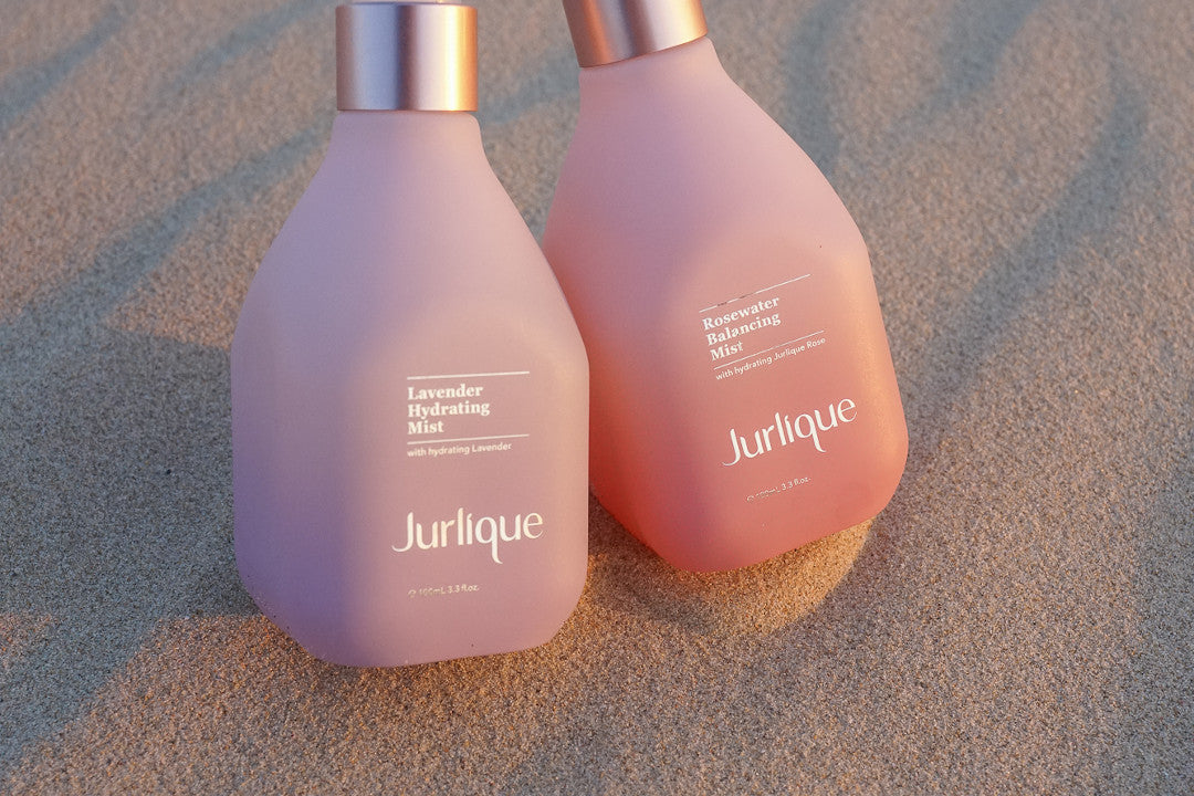 Bottles of Jurlique Lavender Hydrating Mist and Rosewater Balancing Mist next to each other on sand