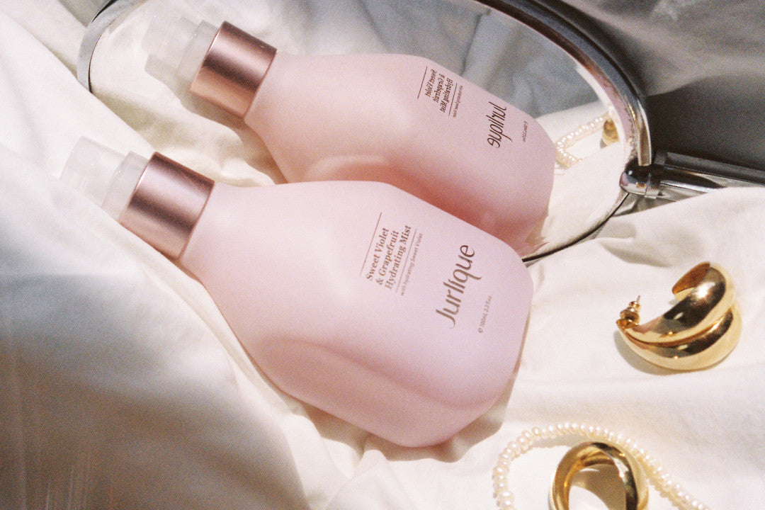 Bottle of Jurlique Sweet Violet & Grapefruit mist on a white sheet with reflection in hand mirror