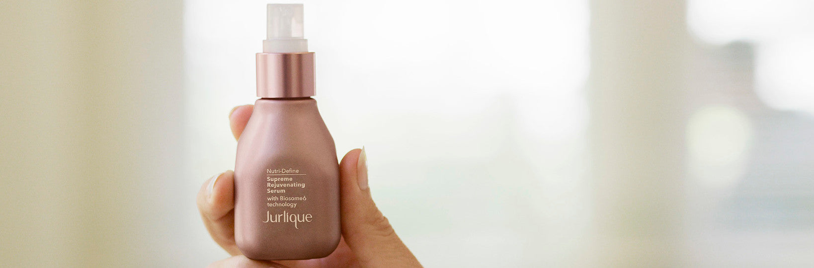Woman's hand holding bottle of Jurlique Nutri-Define Supreme Rejuvenating Serum