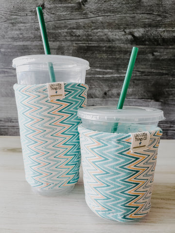 Teal & Yellow Zig-Zag Iced Drink Snug. Tired of sweating iced drink cups?  Or ice just melting too fast in your cold drink?   Insulate your cup with a modern, stylish cup snug.  Keep your coffee cold, hands warm and water rings off the table.  It may also be used on hot cups.
