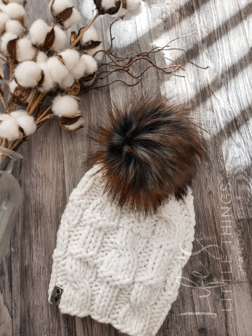 Live. Love. Stay Cozy. Out on the town or on a neighborhood stroll, you will stay warm all fall and winter in this handmade, modern beanie with a large snap on pom-pom to add a little flair.  Merino wool in white.  Topped with a HANDMADE snap on faux fur pom-pom in a black with rust tips.