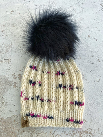 Merino wool in cream with spots of navy and pink.  Topped with a HANDMADE snap on faux fur pom-pom in a very dark navy. Light weight beanie.