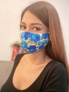 A girl wearing a blue rose printed face mask.
