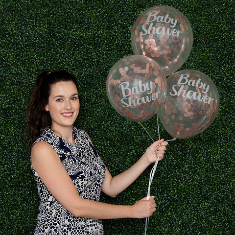 Woman holding inflated baby shower confetti balloons