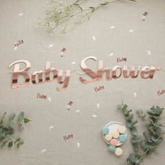 rose gold baby shower banner with macarons and confetti