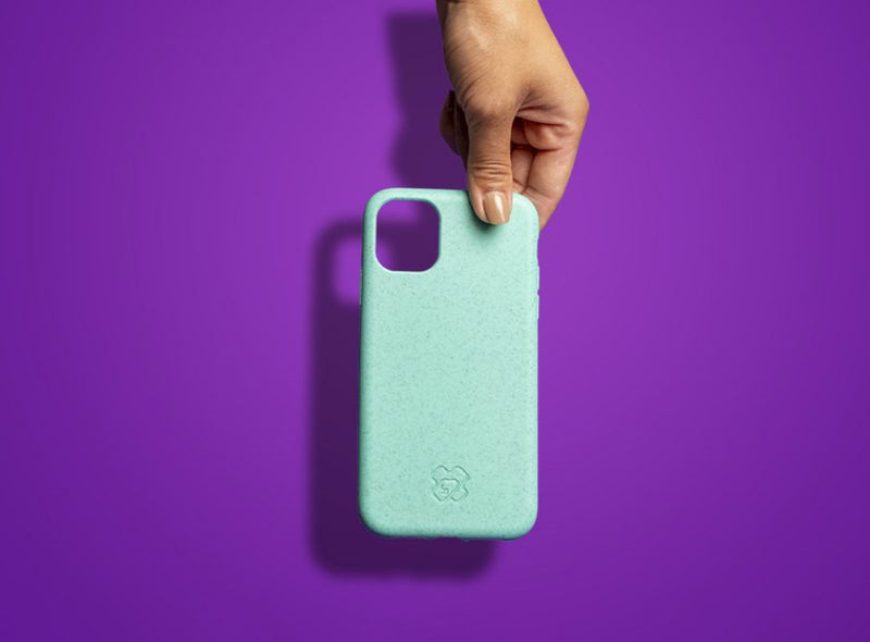 Hand holding a reboxed eco phone case from above against a purple background