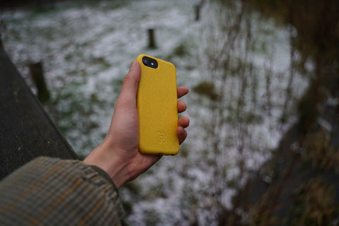 Hand holding an iPhone 12 in an reboxed eco phone case against a backdrop of snow