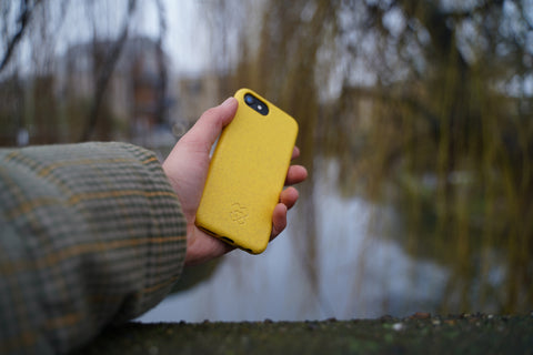 Arm out holding an iPhone 12 in a reboxed eco phone case with a river and trees as background