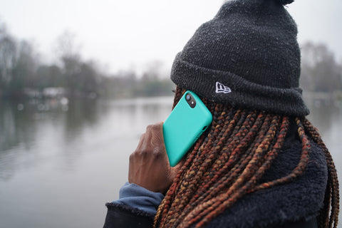Person using Apple iPhone 12 in a reboxed eco phone case against the backdrop of a lake