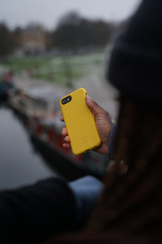 Woman holding an iPhone 12 in a reboxed eco phone case looking down on a river
