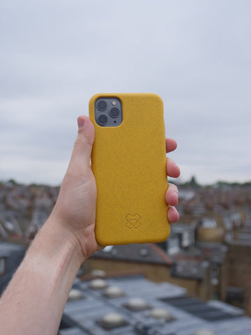 Eco-Yellow reboxed phone case held aloft above a roof