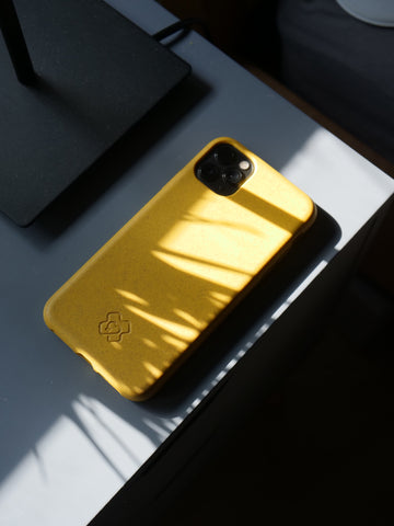 Eco-Yellow reboxed eco phone case lay on the edge of a desk