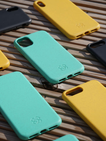 Flat lay of reboxed eco phone cases in Eco Black, Eco Yellow and Eco Green