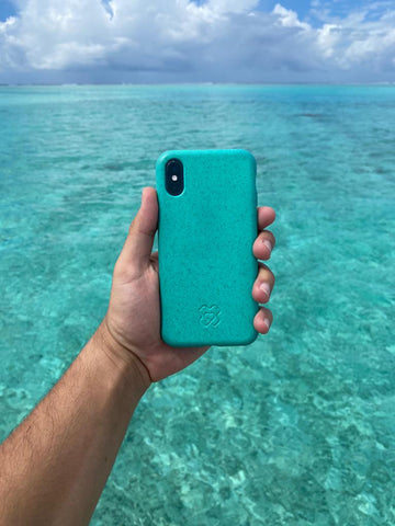 Ocean blue reboxed eco phone case held out over ocean blue sea