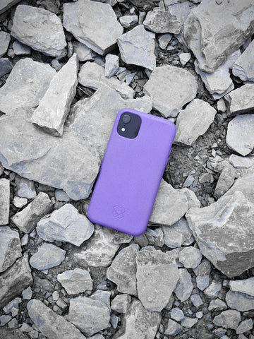 Purple reboxed eco phone case laying face down on a pile of stones