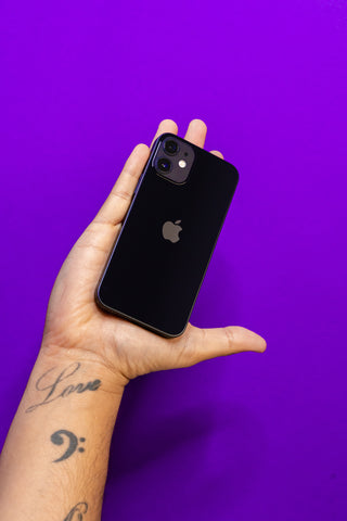 Left hand holding a black iPhone 12 against a reboxed purple background