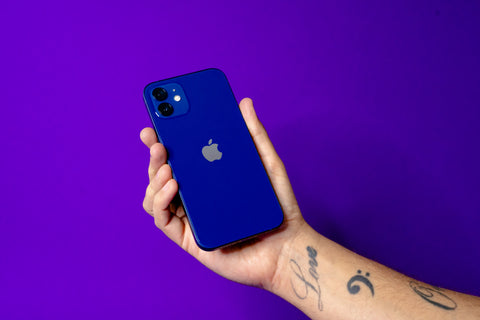 Right hand holding a blue iPhone 12 against a reboxed purple background