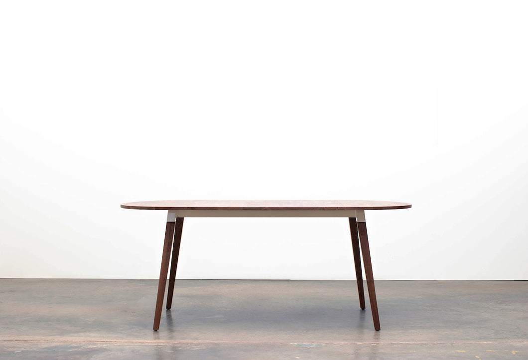 Minimalist Modern Dining Table with Angled Legs. Handmade of Solid Wood and Powder Coated Metal. Available in Walnut, Oak or Ash with Oval or Rectangular Top. Custom Paint Colors Available.