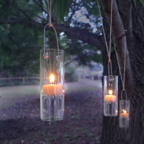 Glass tealight holders hanging from tree for outdoor or alfresco dining lit by beewax teelite candles