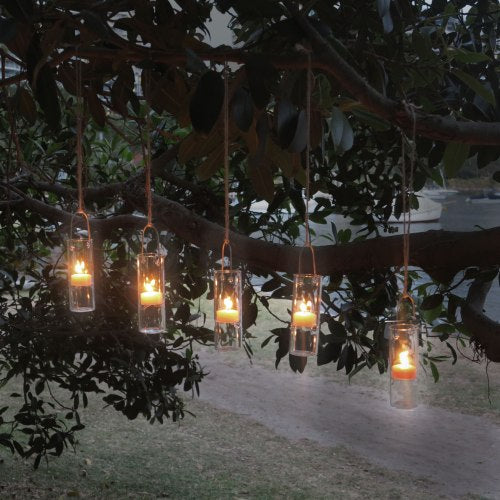Glass candleholders with beeswax tealights in clear cups create a beautiful ambience
